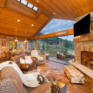 デンバーの広いラスティックスタイルのおしゃれなLDK (無垢フローリング、コーナー設置型暖炉、石材の暖炉まわり、壁掛け型テレビ、茶色い床) の写真