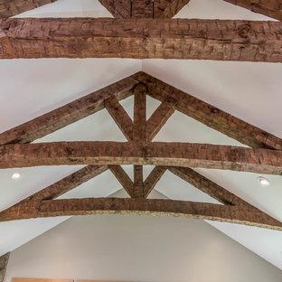 他の地域の中サイズのラスティックスタイルのおしゃれな独立型リビング (グレーの壁、無垢フローリング、両方向型暖炉、石材の暖炉まわり、テレビなし、茶色い床) の写真