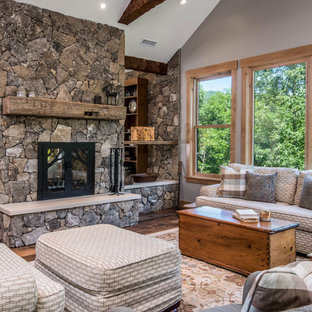 This is an example of a medium sized rustic enclosed living room in Other with grey walls, medium hardwood flooring, a two-sided fireplace, a stone fireplace surround, brown floors and no tv.
