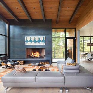Imagen de salón abierto, rústico, grande, sin televisor, con paredes negras, suelo de madera clara y marco de chimenea de piedra