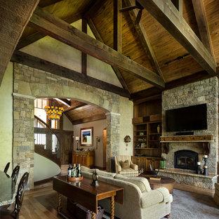 カンザスシティの大きいラスティックスタイルのおしゃれなLDK (淡色無垢フローリング、標準型暖炉、石材の暖炉まわり、壁掛け型テレビ) の写真