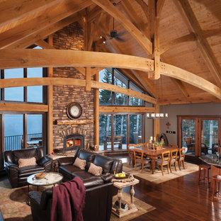 Modelo de salón abierto, rústico, grande, con marco de chimenea de piedra, suelo de madera oscura, paredes marrones y estufa de leña