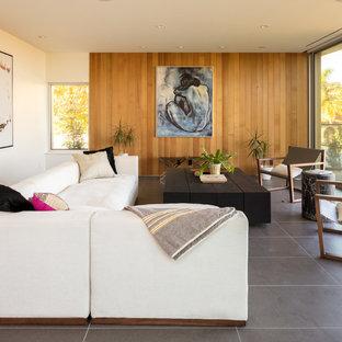 Bild på ett mellanstort funkis allrum med öppen planlösning, med vita väggar, klinkergolv i keramik, en dold TV och grått golv