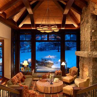 デンバーの巨大なラスティックスタイルのおしゃれなリビング (スレートの床、標準型暖炉、石材の暖炉まわり) の写真