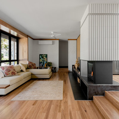 Living room - large 1950s open concept medium tone wood floor and brown floor living room idea in Other with white walls, a two-sided fireplace, a tile fireplace and a tv stand