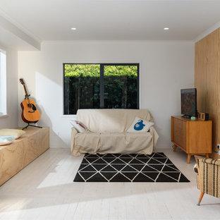Ejemplo de salón abierto, costero, sin chimenea, con paredes blancas, suelo de madera pintada, televisor independiente y suelo turquesa