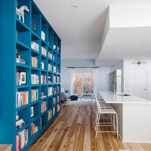 Inredning av ett minimalistiskt stort allrum med öppen planlösning, med vita väggar, ljust trägolv och ett bibliotek