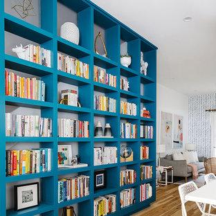 Réalisation d'un grand salon avec une bibliothèque ou un coin lecture nordique ouvert avec un mur blanc, un sol en bois clair, aucune cheminée et aucun téléviseur.