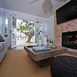 サンディエゴの中くらいのビーチスタイルのおしゃれなLDK (フォーマル、マルチカラーの壁、濃色無垢フローリング、標準型暖炉、石材の暖炉まわり、壁掛け型テレビ、茶色い床) の写真
