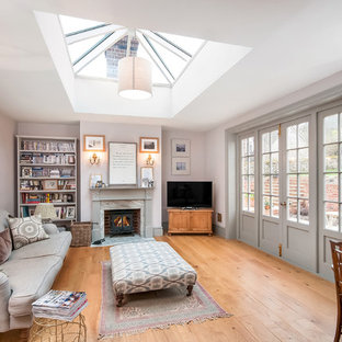 Large classic enclosed living room in Hampshire with a reading nook, grey walls, medium hardwood flooring, a wood burning stove, a wooden fireplace surround, brown floors and a freestanding tv.