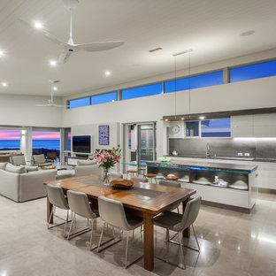 パースの大きいビーチスタイルのおしゃれなLDK (白い壁、トラバーチンの床、標準型暖炉、漆喰の暖炉まわり、壁掛け型テレビ、ベージュの床) の写真