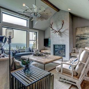 Ejemplo de salón abierto, de estilo de casa de campo, grande, con paredes grises, suelo laminado, marco de chimenea de yeso, televisor colgado en la pared, suelo gris y chimenea tradicional