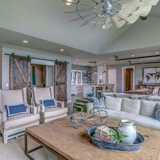 Design ideas for a large country open concept living room in Other with grey walls, laminate floors, a hanging fireplace, a plaster fireplace surround, a wall-mounted tv and grey floor.