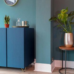 Esempio di un soggiorno minimalista di medie dimensioni e chiuso con angolo bar, pareti blu, pavimento in laminato, nessun camino, cornice del camino in legno, TV a parete e pavimento marrone