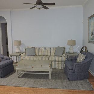 Example of a mid-sized transitional enclosed medium tone wood floor and beige floor living room design in Other with blue walls and no fireplace