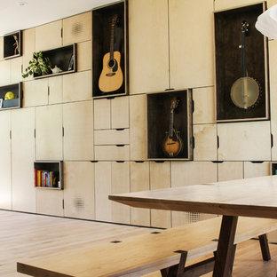 Ejemplo de biblioteca en casa abierta, contemporánea, pequeña, sin chimenea, con suelo de madera clara, televisor retractable y paredes blancas