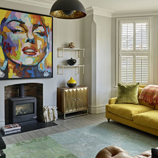 Inspiration for a contemporary formal enclosed living room in London with grey walls, medium hardwood flooring, a wood burning stove, a metal fireplace surround and grey floors.