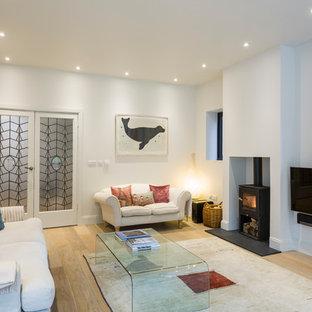Modelo de salón nórdico con televisor colgado en la pared, suelo de madera clara, paredes blancas y estufa de leña
