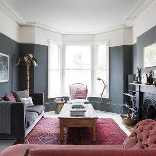Foto de salón para visitas cerrado, actual, con paredes negras, suelo de madera pintada, chimenea tradicional y suelo blanco