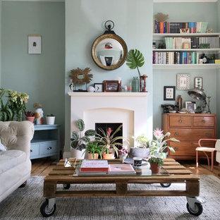 Abgetrenntes, Kleines Stilmix Wohnzimmer mit grüner Wandfarbe, Kamin, Kaminsims aus Stein, freistehendem TV, braunem Holzboden und braunem Boden in London