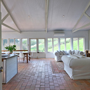Example of a cottage open concept brick floor living room design in Adelaide with white walls
