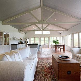 Idee per un grande soggiorno country aperto con pavimento in mattoni
