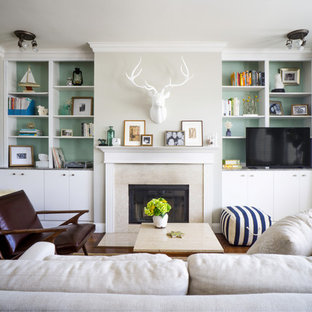 Example of a transitional formal living room design in San Francisco with green walls, a standard fireplace and a tv stand