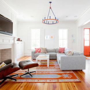 チャールストンのエクレクティックスタイルのおしゃれな独立型リビング (フォーマル、白い壁、無垢フローリング、標準型暖炉、石材の暖炉まわり、壁掛け型テレビ、オレンジの床) の写真