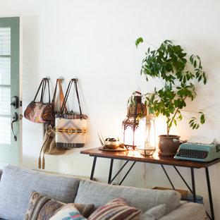 Cette photo montre un petit salon sud-ouest américain fermé avec un mur blanc, un sol en bois brun, une cheminée standard, un manteau de cheminée en brique et un téléviseur indépendant.