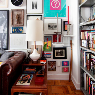 Example of an eclectic medium tone wood floor living room design in Boston with white walls