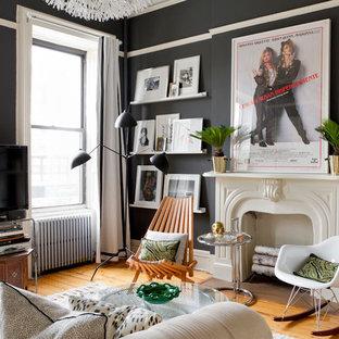 Foto de salón bohemio con paredes negras, suelo de madera en tonos medios, chimenea tradicional y televisor independiente