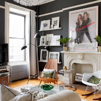 Example of an eclectic medium tone wood floor living room design in New York with black walls, a standard fireplace and a tv stand