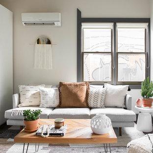 ナッシュビルのサンタフェスタイルのおしゃれな独立型リビング (ベージュの壁、茶色い床) の写真