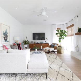 Diseño de salón tradicional renovado con paredes blancas, chimenea tradicional, televisor colgado en la pared, suelo beige, suelo de madera clara y marco de chimenea de ladrillo
