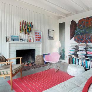 他の地域のエクレクティックスタイルのおしゃれな独立型リビング (フォーマル、白い壁、コンクリートの床、標準型暖炉、レンガの暖炉まわり、テレビなし、グレーの床) の写真