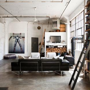 Esempio di un soggiorno industriale con pavimento in cemento