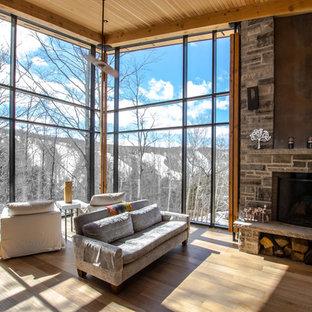 Diseño de salón abierto, contemporáneo, extra grande, sin televisor, con paredes blancas, suelo de madera clara, chimenea tradicional y marco de chimenea de piedra