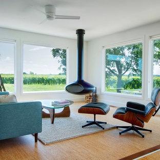 Bild på ett funkis vardagsrum, med korkgolv, en hängande öppen spis och vita väggar