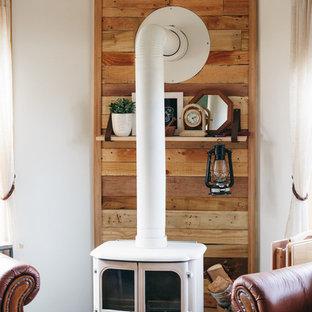 Modelo de salón cerrado, de estilo de casa de campo, de tamaño medio, con paredes blancas, suelo de madera en tonos medios, estufa de leña y marco de chimenea de madera