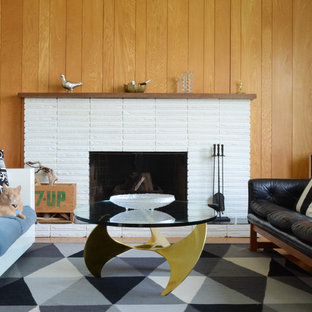 This is an example of a midcentury living room in Vancouver with a standard fireplace and a brick fireplace surround.
