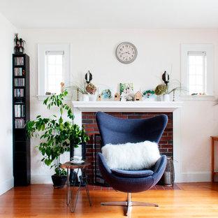 Klassisk inredning av ett vardagsrum, med rosa väggar, mellanmörkt trägolv, en standard öppen spis, en spiselkrans i tegelsten och brunt golv