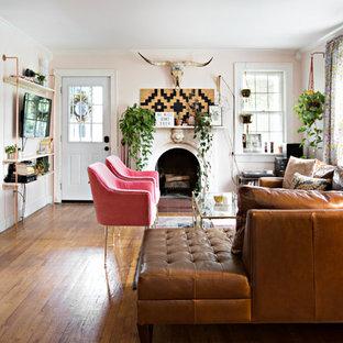 Esempio di un soggiorno bohémian chiuso con pareti rosa, pavimento in legno massello medio, camino classico, cornice del camino in intonaco, TV a parete e pavimento marrone