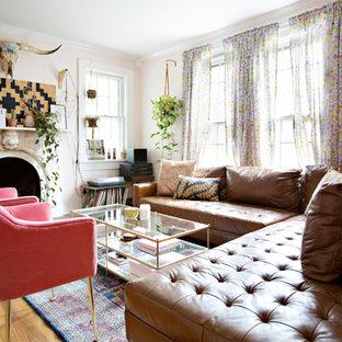 Abgetrenntes Stilmix Wohnzimmer mit rosa Wandfarbe, braunem Holzboden, Kamin, verputzter Kaminumrandung, Wand-TV und braunem Boden in Nashville