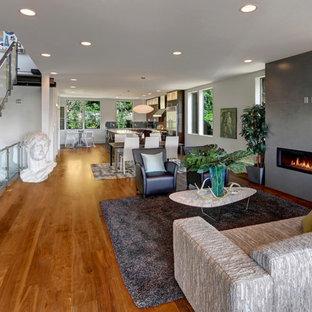 シアトルの中サイズのトロピカルスタイルのおしゃれなLDK (グレーの壁、無垢フローリング、横長型暖炉、コンクリートの暖炉まわり、茶色い床) の写真