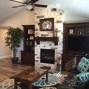 ソルトレイクシティの中サイズのトラディショナルスタイルのおしゃれなLDK (フォーマル、ベージュの壁、塗装フローリング、吊り下げ式暖炉、石材の暖炉まわり、埋込式メディアウォール、マルチカラーの床) の写真