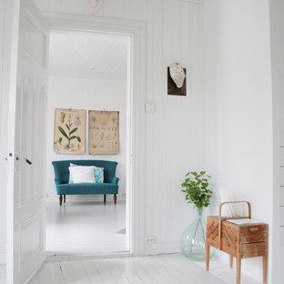 Modelo de salón nórdico con paredes blancas, suelo de madera pintada y suelo blanco