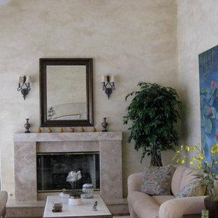 サンフランシスコの中くらいの地中海スタイルのおしゃれなLDK (フォーマル、ベージュの壁、無垢フローリング、標準型暖炉、コンクリートの暖炉まわり、テレビなし、茶色い床) の写真