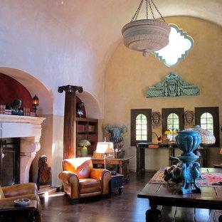 サンフランシスコの小さい地中海スタイルのおしゃれなLDK (フォーマル、ベージュの壁、濃色無垢フローリング、標準型暖炉、コンクリートの暖炉まわり、テレビなし、茶色い床) の写真
