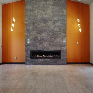Immagine di un grande soggiorno contemporaneo aperto con pareti arancioni, camino classico, cornice del camino piastrellata, sala formale, pavimento in laminato, nessuna TV e pavimento beige