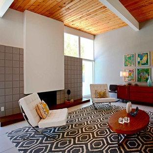 ロサンゼルスの中サイズのミッドセンチュリースタイルのおしゃれなLDK (白い壁、磁器タイルの床、標準型暖炉、コンクリートの暖炉まわり、テレビなし) の写真